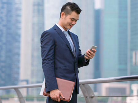 Businessman standing outdoors and using his phone