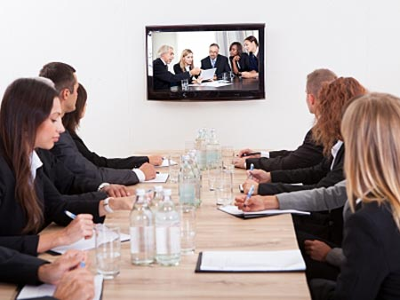 Businesspeople-Sitting-At-Conference-Table-Looking-At-Flat-Screen-Display