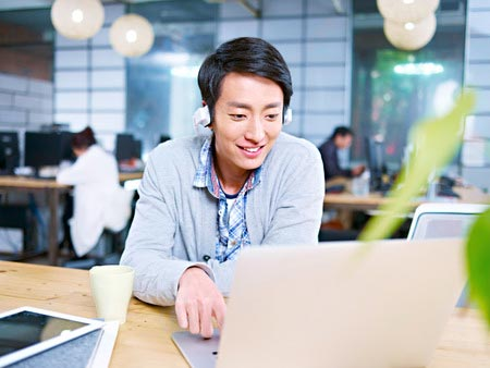 young asian businessman sitting at desk in office